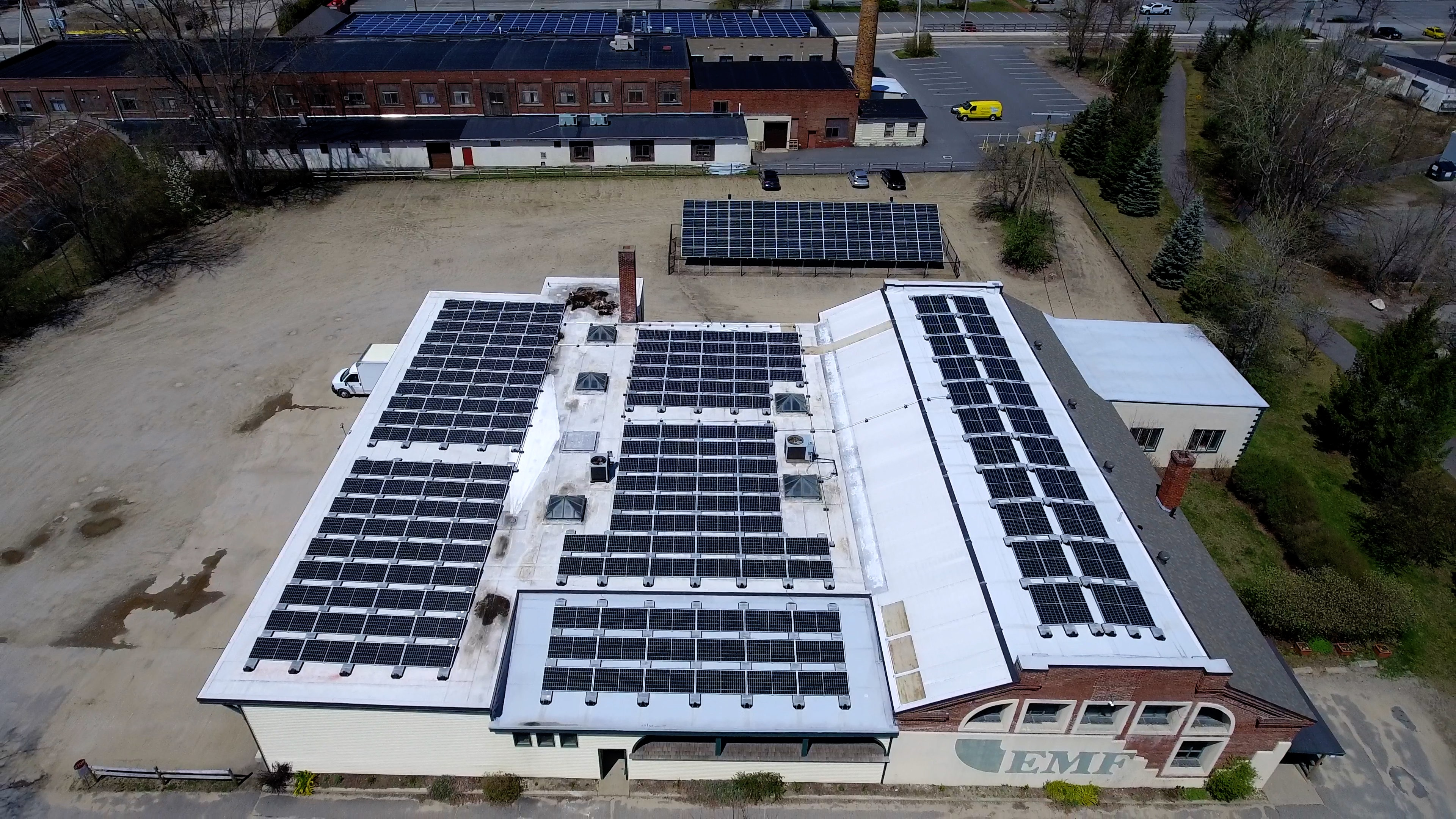 View of two buildings with roof solar installations and a ground installation