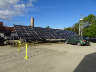 Ground installation of solar panels next to a car
